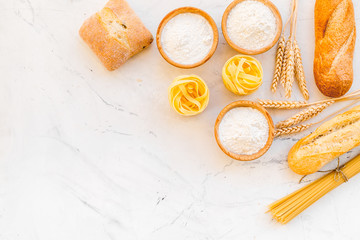 Farinaceous food. Fresh bread and raw pasta near flour in bowl and wheat ears on white stone background top view space for text