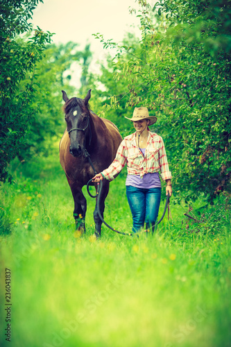 Western woman walking on green meadow with horse