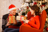 Image of man in Santa cap with gift and pregnant woman