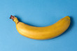 Minimalism style. Ripe yellow banana over blue background. - 236050049