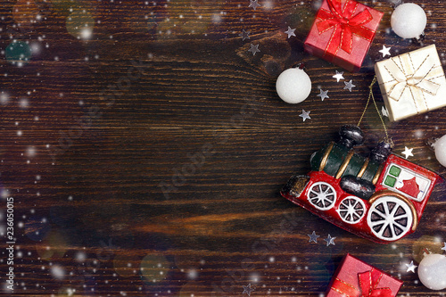 Winter holiday background with toy train, gift boxes and copy space on wooden table. - 236050015