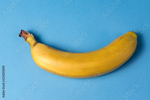 Minimalism style. Ripe yellow banana over blue background. - 236050049