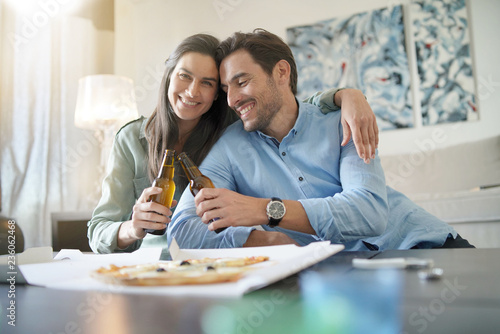 Happy relaxed couple sharing a pizza at home - 236062468