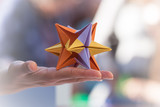 Hand holding and showing a colorful modular origami star. Lightness concept.