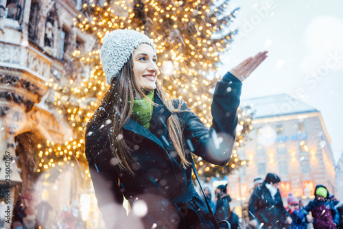 Plakat Woman enjoying Christmas time in the city while it is snowing