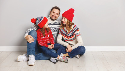 happy family mother, father and child daughter in knitted hats and sweaters on gray background.