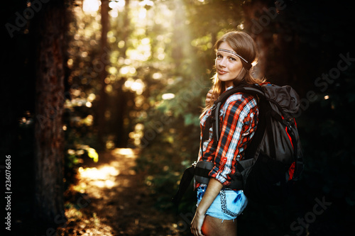 Beautiful and young woman hiking in forest
