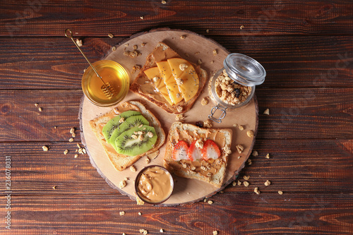 Leinwandbild Motiv Board with different delicious toasts and honey on wooden table