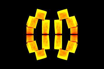 Construction of yellow cubes. Imitation of hot metal. Reflection and repetition of elements. Isolated on black background. Abstract texture.