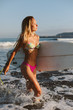 Beautiful surfer in the sea running with her surfboard