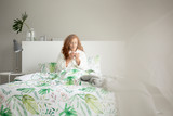 Young woman sitting on double bed with leafy sheets in bright bedroom interior with books, decor and grey lamp - 236103421