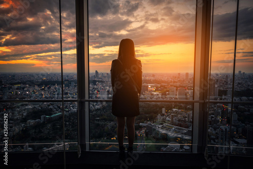 fototapeta na ścianę Rear view of Traveler woman looking Tokyo Skyline and view of skyscrapers on the observation deck at sunset in Japan.