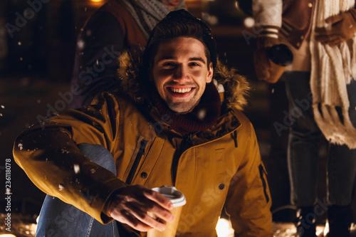 Leinwandbild Motiv Happy young handsome man sitting outdoors in evening.