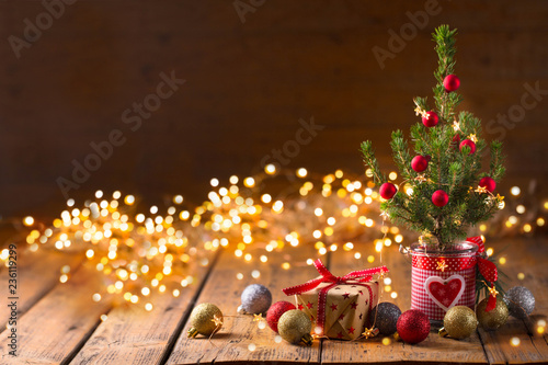 Little Christmas tree with gift boxes on rustic wood