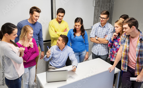 education, high school, technology and people concept - group of students and teacher with papers and laptop computer in classroom