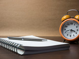 alarm clock and notebook on table