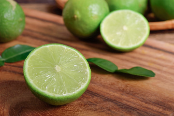 whole and half cut fresh lime with leaf on wooden background