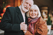 Portrait of happy bearded gentleman hugging his lovely wife and holding her hand. They looking at camera and smiling