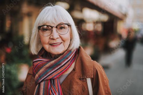 Leinwandbild Motiv Portrait of stylish old lady in coat looking at camera and smiling. Street on blurred background