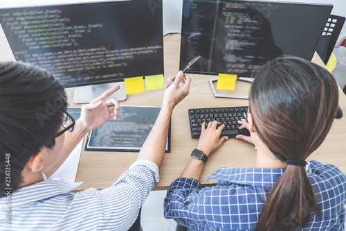 Leinwanddruck Bild Two professional programmers cooperating at Developing programming and website working in a software develop company office, writing codes and typing data code