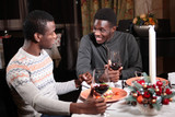 Two African Americans in a restaurant at the new year's table. Holding glasses of red wine. The guy on the left is out of focus. The concept of friendship and rest. - 236151040
