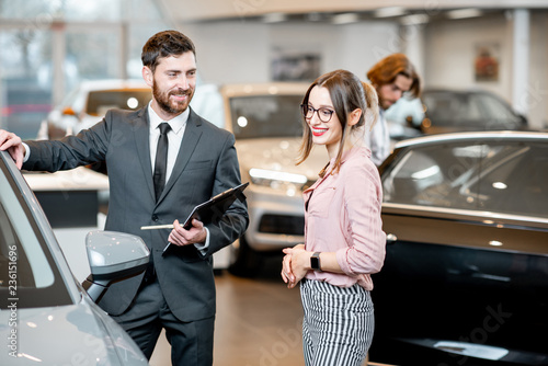 Leinwandbild Motiv Car salesman helping to a young woman client to make decision showing a new car at the showroom