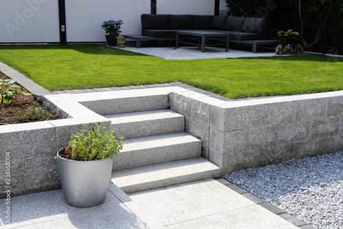 Leinwandbild Motiv Gepflegter Ziergarten mit Granitmauer und Blockstufentreppe