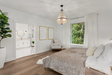 Beautiful Bedroom in New Luxury Home with View of Master Bathroom. Features Hardwood Floors and Pendant Light Fixture.