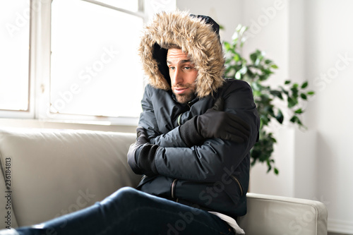 Leinwanddruck Bild A Man have cold on the sofa at home with winter coat