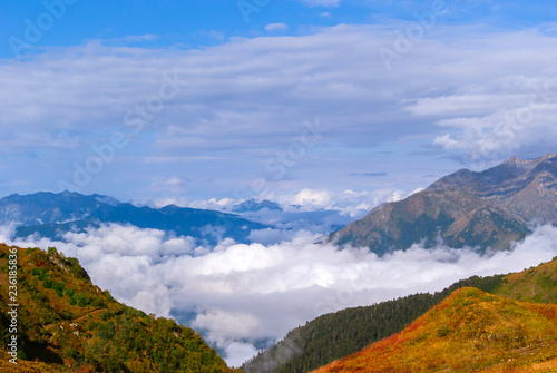 landscape - view from the mountain top on a sunny day to the valley hidden by low clouds - 236185836