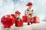 Portrait of adroable twin-elves among huge Christmas presents - 236186472