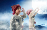 Portrait of two adorbale twin brothers looking at the Christmas sky - 236186490