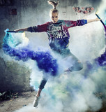 Portrait of a jumping dancer holding colorful flares - 236186655