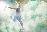 Portrait of a jumping dancer holding colorful flares - 236186667