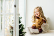 Leinwandbild Motiv little girl with a plush deer sitting on the window. A child looks out the window and is waiting for Christmas, Santa Claus