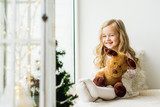 little girl with a plush deer sitting on the window. A child looks out the window and is waiting for Christmas, Santa Claus