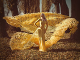 Portrait of a blonde wearing a flowery, golden gown - 236195873