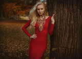 Pretty blond woman posing in an autumnal park - 236196090
