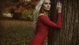 Pretty blond woman posing in an autumnal park - 236196225