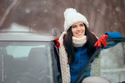Leinwandbild Motiv Happy Female Driver Standing By Her Car Admiring the Snow