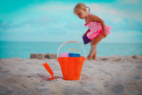 kids toys and little girl playing on beach
