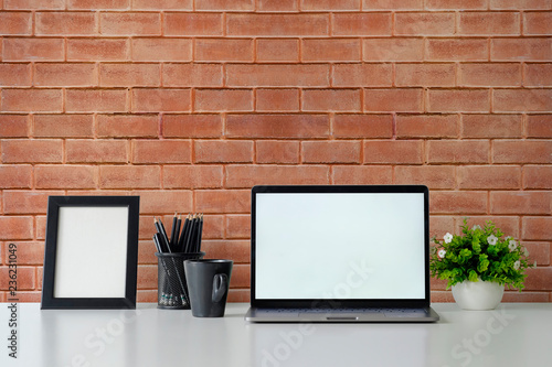 Mockup laptop computer, photo frame,  coffee and plant decoration on office table and brick wall background. - 236231049