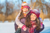 Little girl and her mother playing outdoors at sunny winter day - 236232071