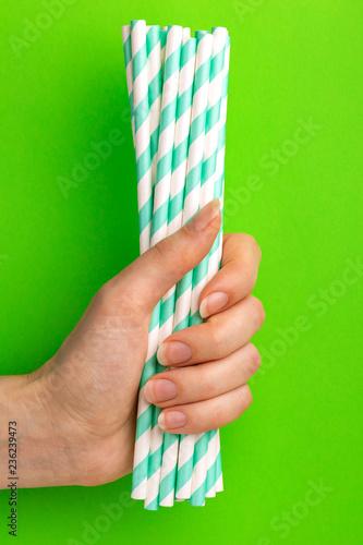 Leinwandbild Motiv Woman is holding green and white paper straws in hand