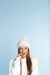 Cute thinking young woman wearing winter hat posing isolated over blue wall background.