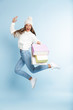 Cute young woman wearing winter hat jumping isolated over blue wall background holding holding bags.