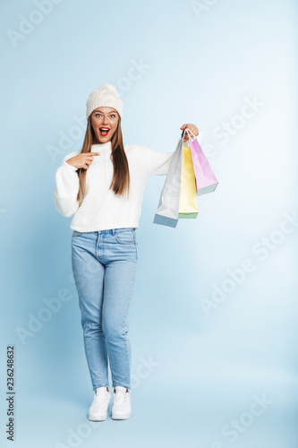 Leinwandbild Motiv Cute young woman wearing winter hat isolated over blue wall background holding holding shopping bags.