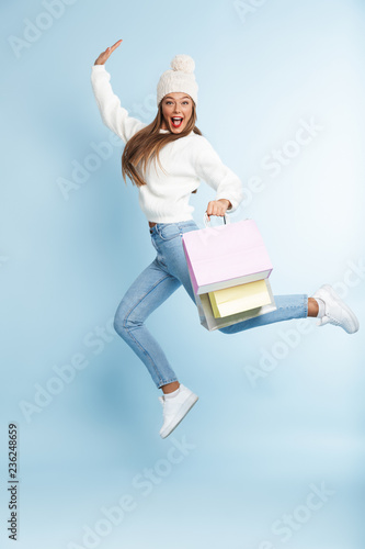 Leinwandbild Motiv Cute young woman wearing winter hat jumping isolated over blue wall background holding holding bags.
