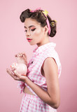 loan. Money. Housewife. pretty girl in vintage style. pinup girl with fashion hair. pin up woman with trendy makeup. retro woman with moneybox. Money and power