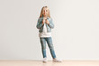 Full length portrait of cute little kid girl in stylish jeans clothes looking at camera and smiling, standing against white studio wall. Kids fashion concept